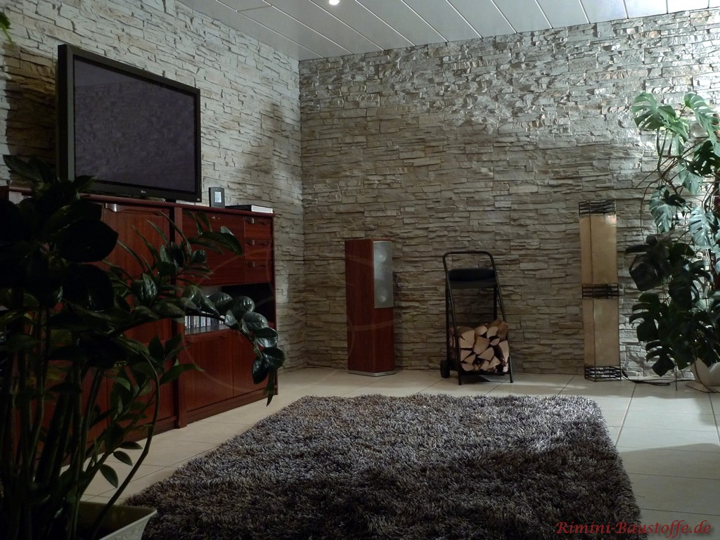 Wohnzimmer in grauer Natursteinoptik mit Möbeln aus dunklem Holz