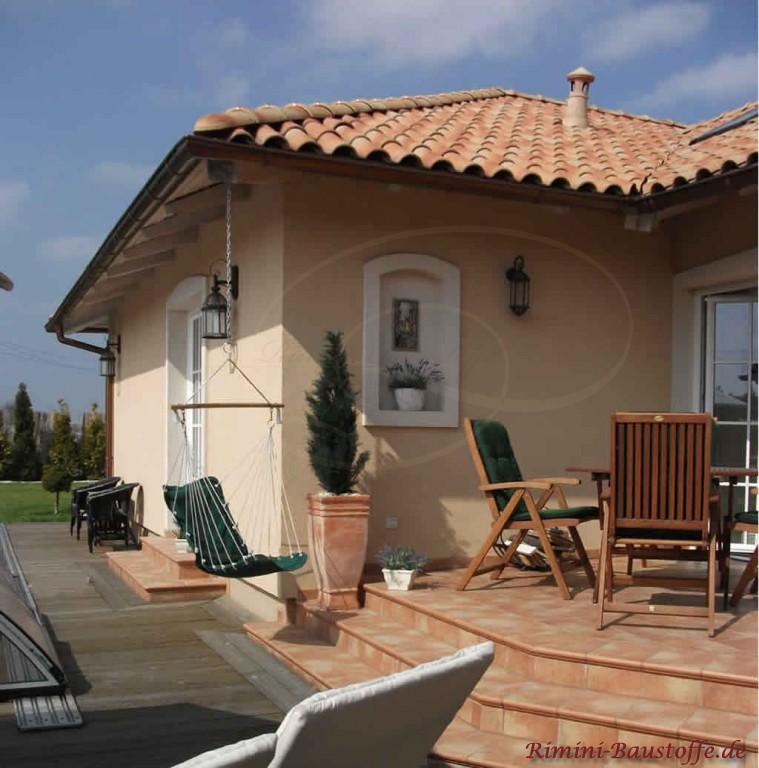 passend zum Haus eine Terrasse mit Terracottafliesen und Wandverzierungen