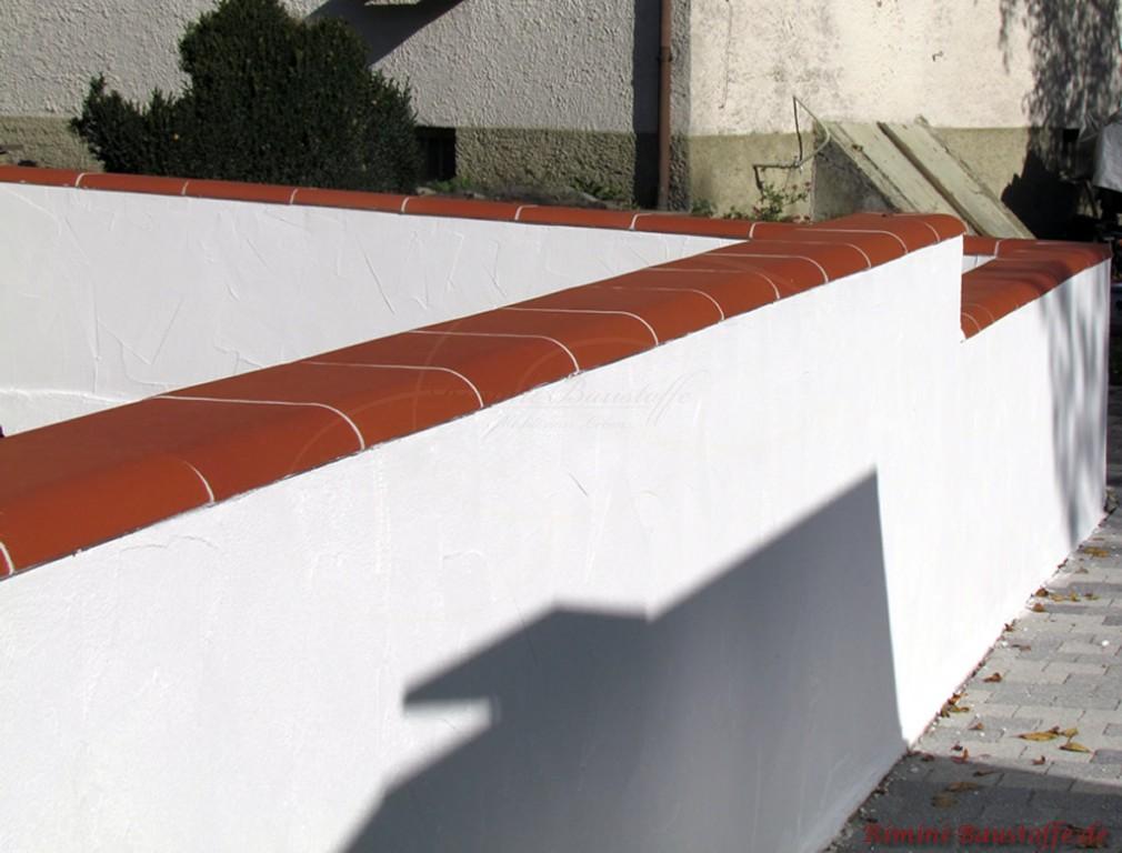 kräftige rote Mauerabdeckung mit heller Fuge auf einer weissen Putzmauer
