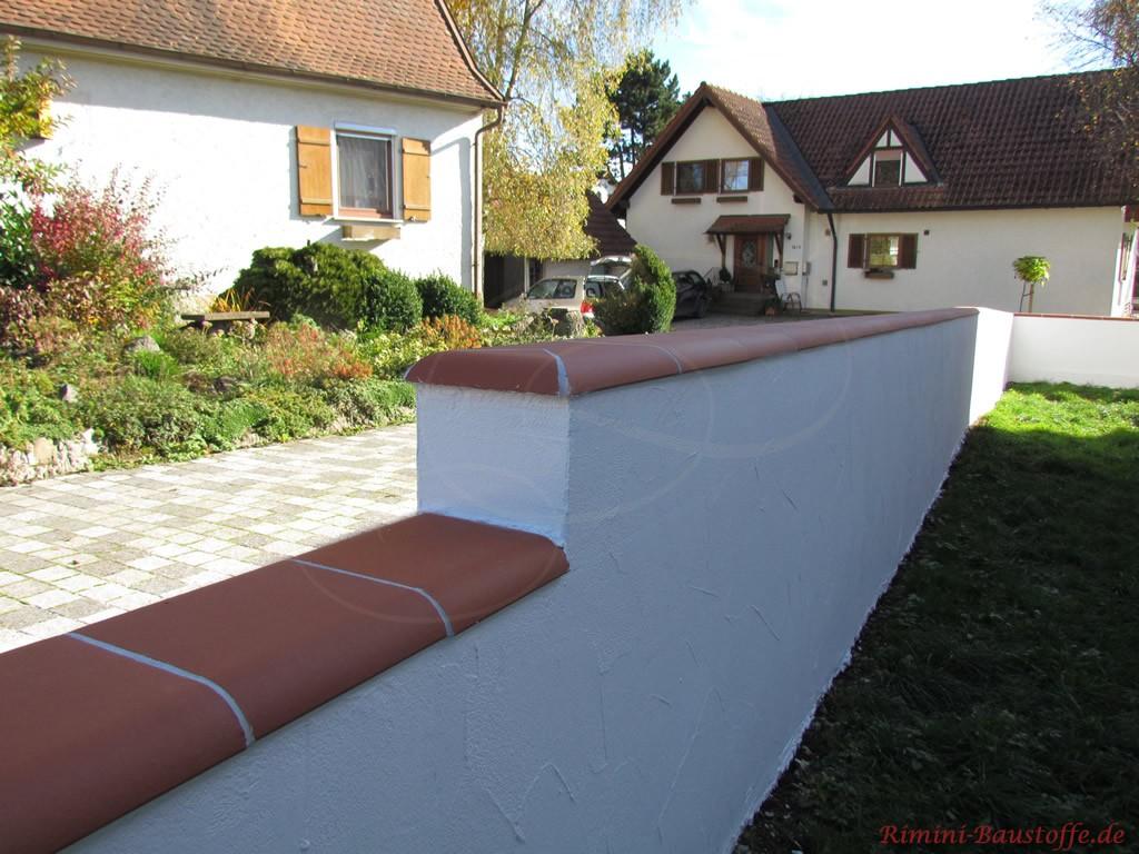 Mauer mit weissem Strukturputz und glatter, roter Mauerabdeckung
