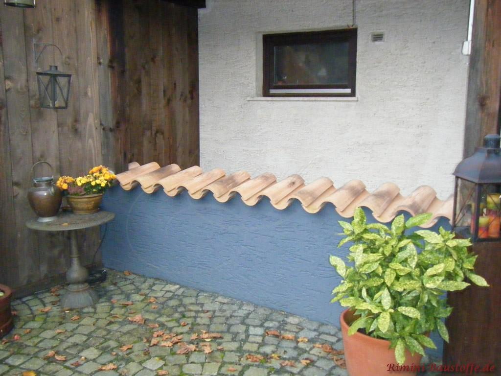 graue Mauer mit Strukturputz und beiger Mauerabdeckung