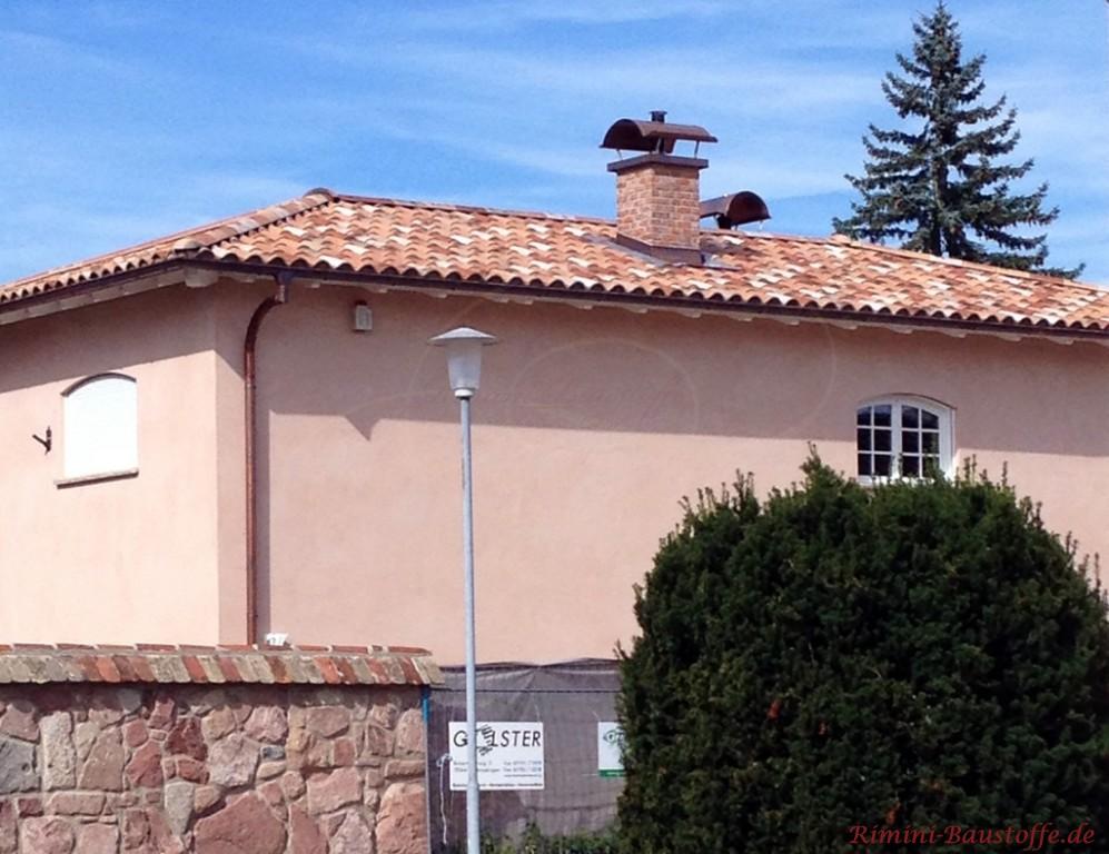 große zweigeschossige Villa mit Natursteinmauer
