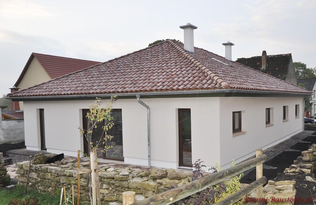 Bungalow mit heller Putzfassade und Walmdach im mediterranen Stil