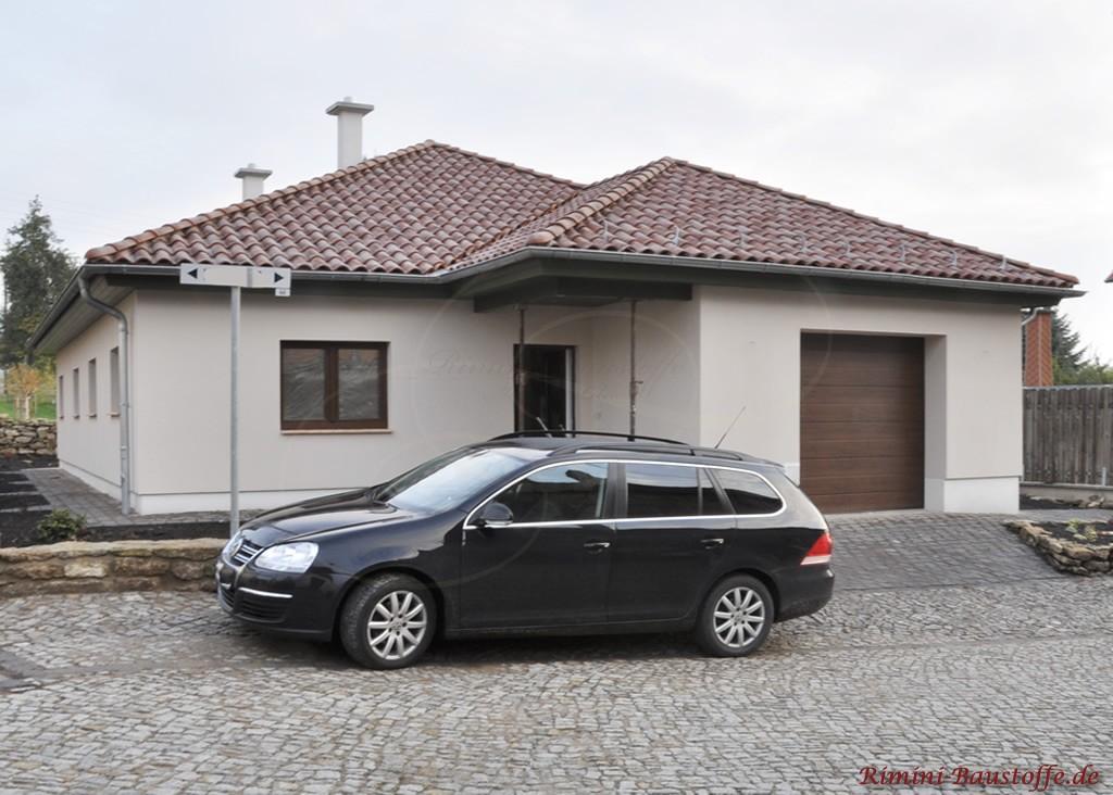 kleiner Bungalow mit heller Putzfassade und braunen Fenstern + Garagentor