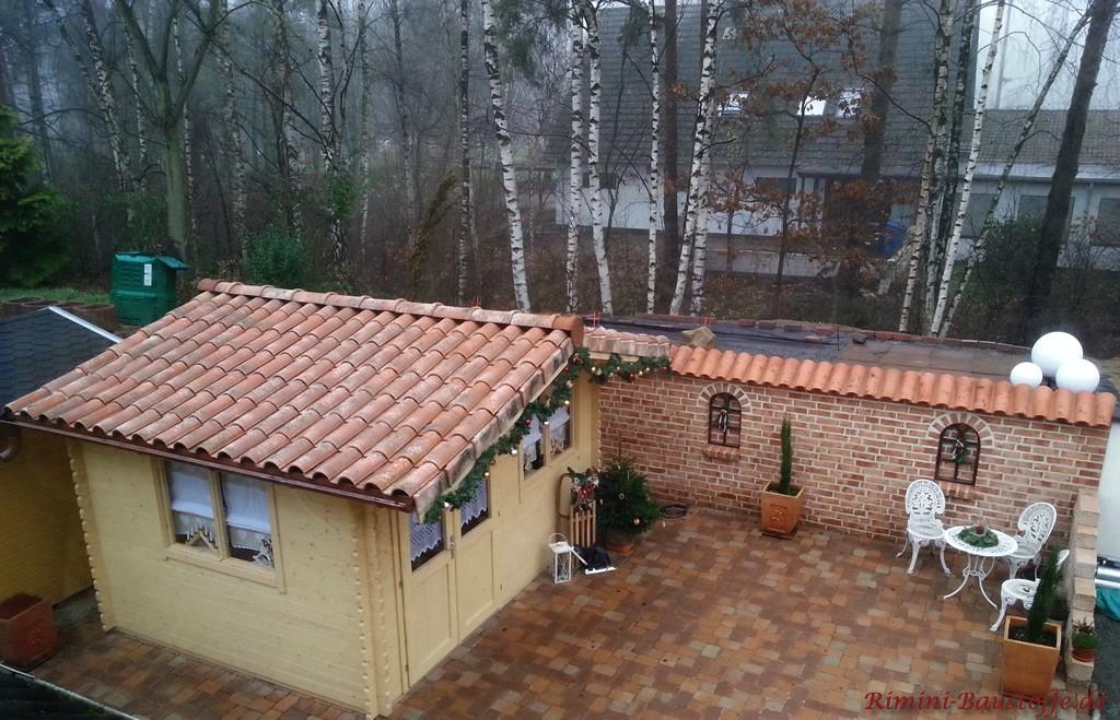Mediterrane Gartenecke mit Gartenhaus und Mauer
