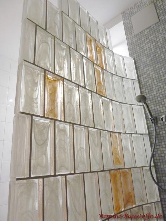 Duschwand aus Muranoglaselementen mit einzelnen farbigen Steinen