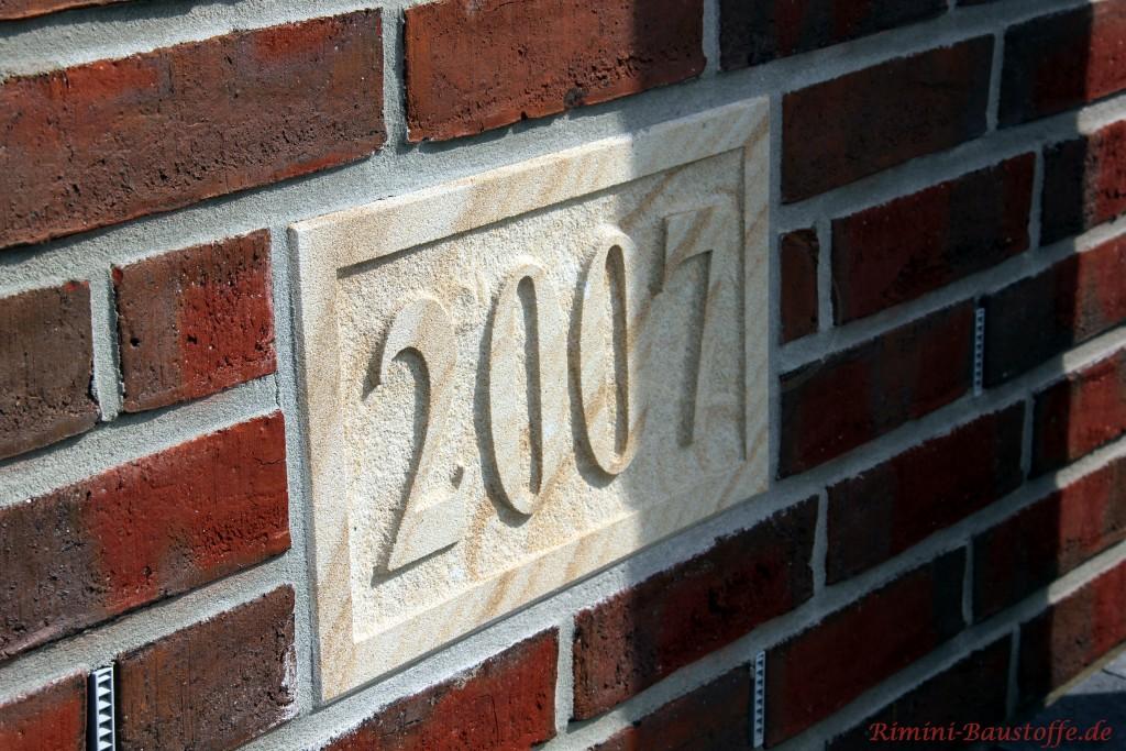 Hausnummer aus Sandstein in einer Klinkerfassade