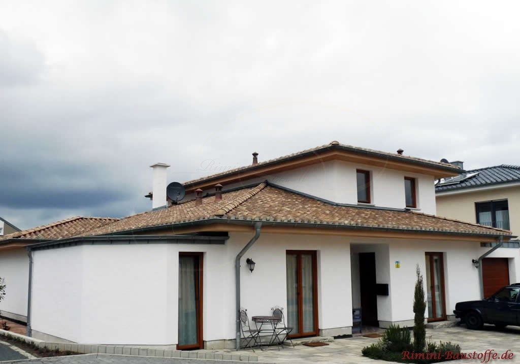 Putzbau mit weisser Fassade und sehr antikem braunen Dachziegel