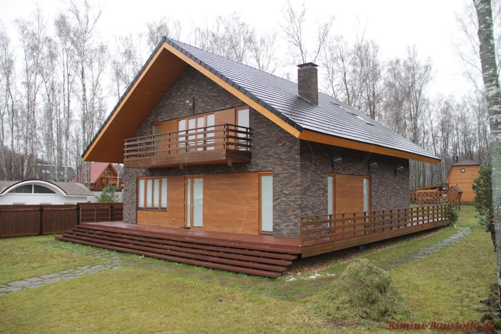 Satteldachhaus mit Holzelementen zur dunklen Klinkerfassade