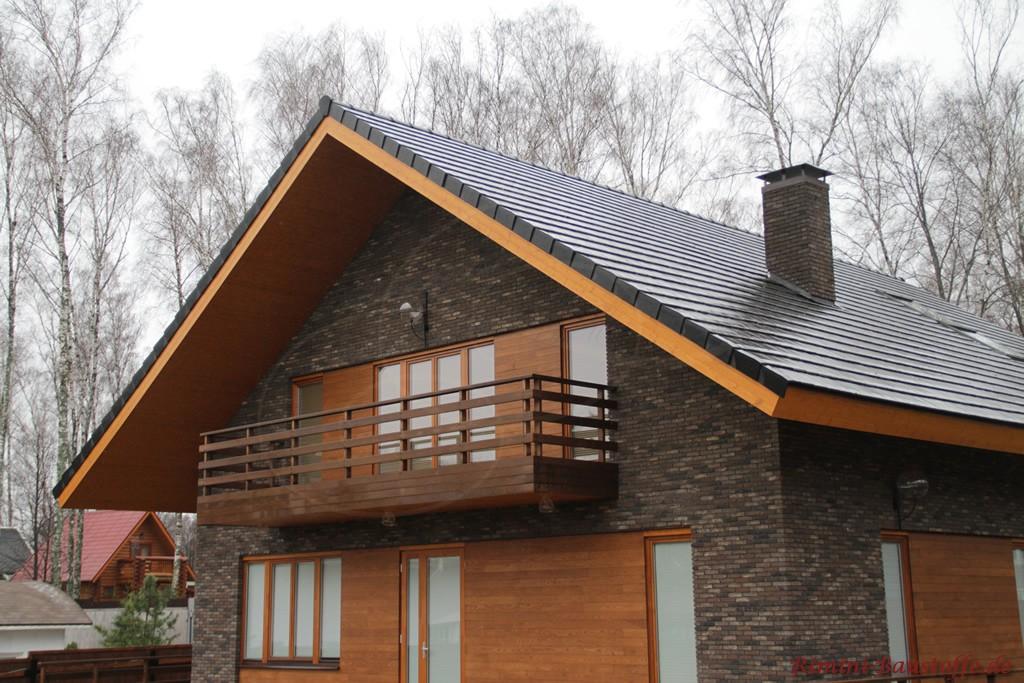 dunkler feiner Klinker mit Holzelementen in der Fassade