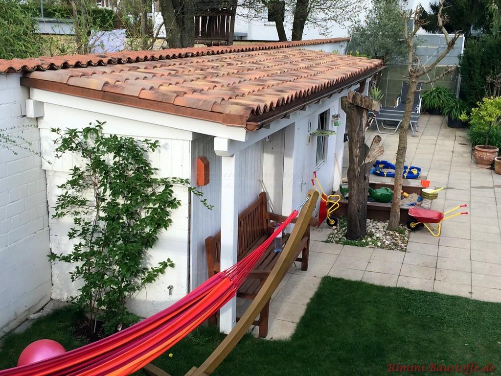 kleines Gartenhaus schließt an die Gartenmauer an