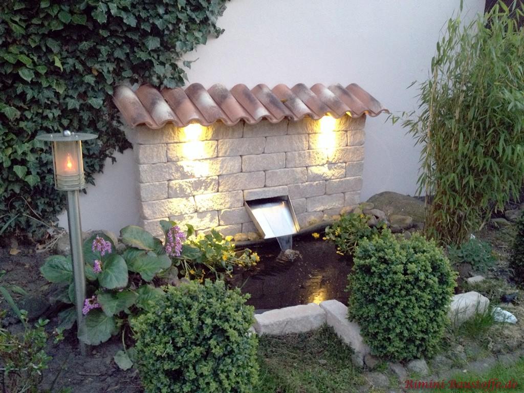 kleine beleuchtete Ziermauer an einem Gartenteich