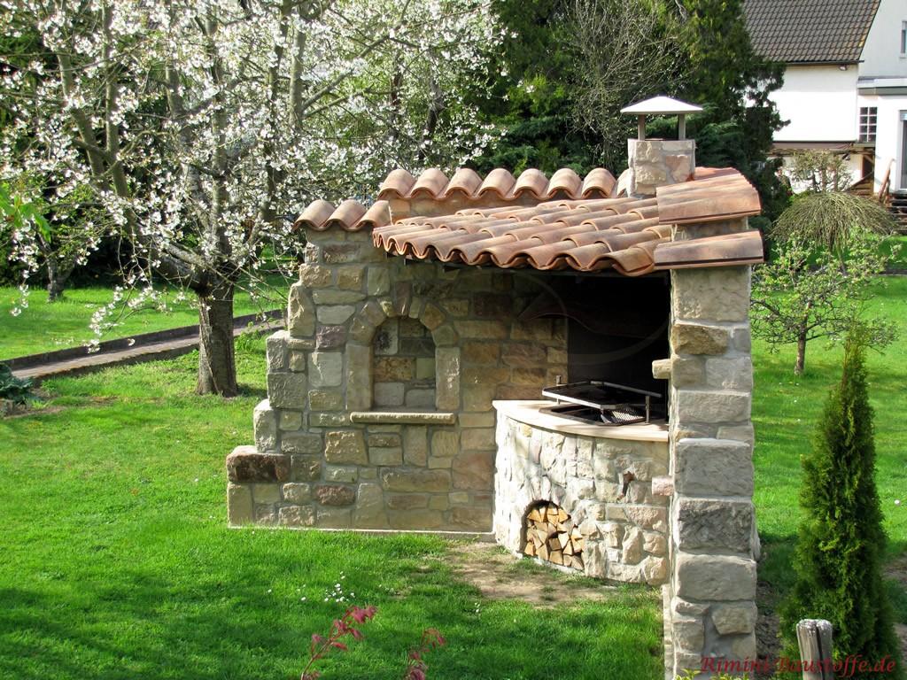 überdachter Gartengrill in eine Eckmauer integriert