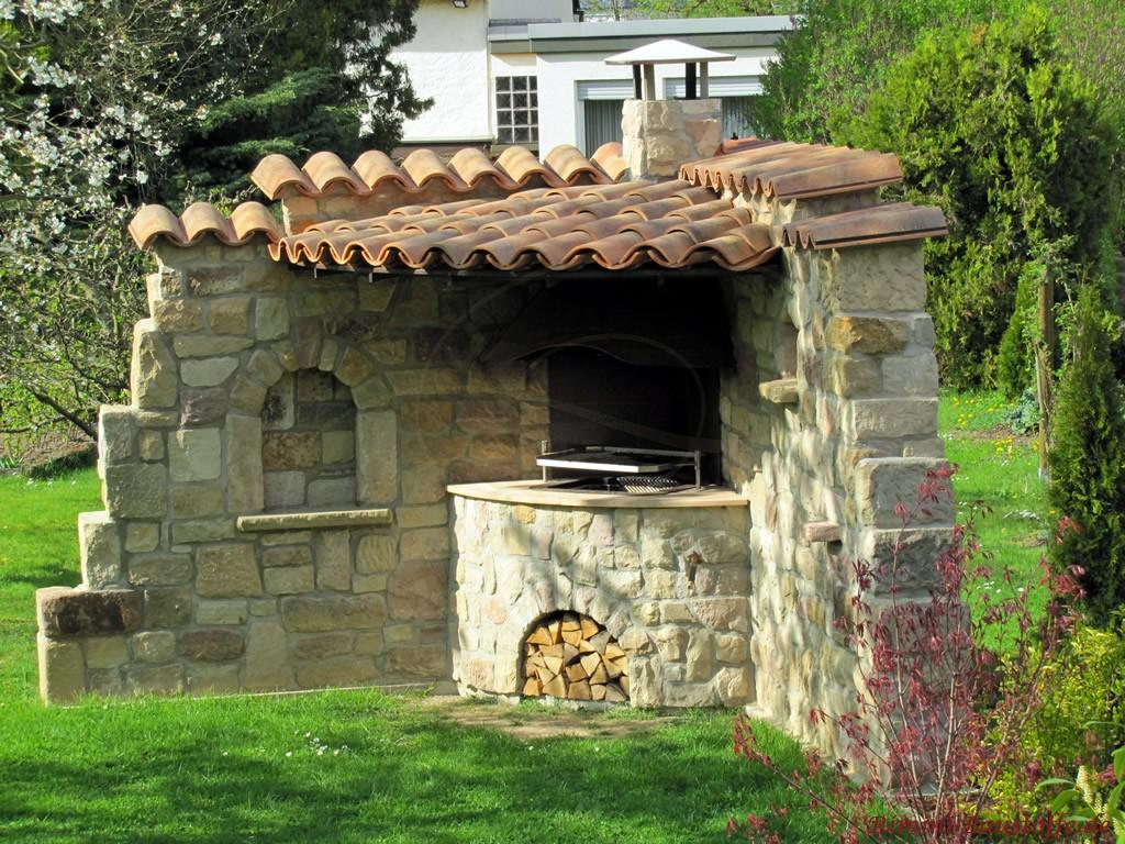 Gartengrill in eine Eckmauer aus Natursteinen ingegriert mit Überdachung