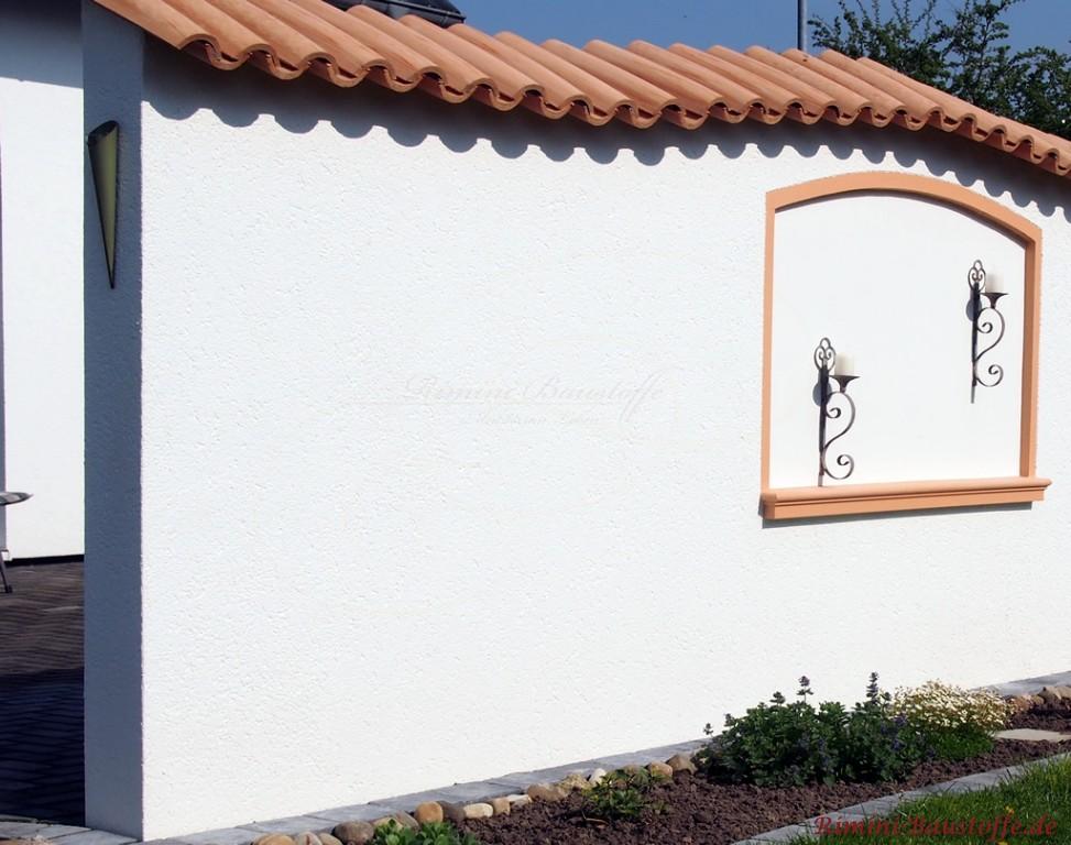verzierte Gartenmauer aus weissem Putz und heller Mauerabdeckung