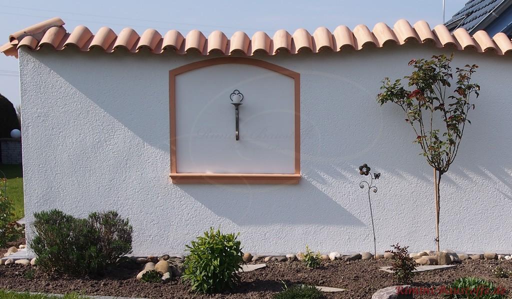 Gartenmauer mit schöner Stuckverzierung und einer Wandlampe
