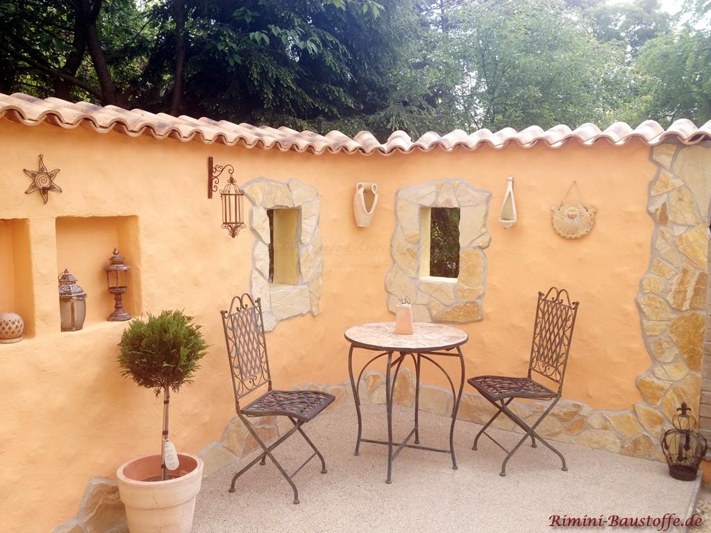 Gartenecke im mediterranen Stil mit gelber Putzmauer
