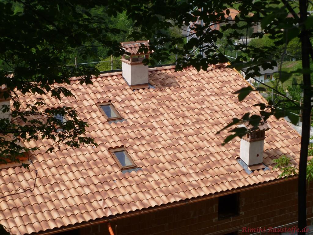 Satteldach mit kleinen Dachfenstern und verputzten Schornsteinen