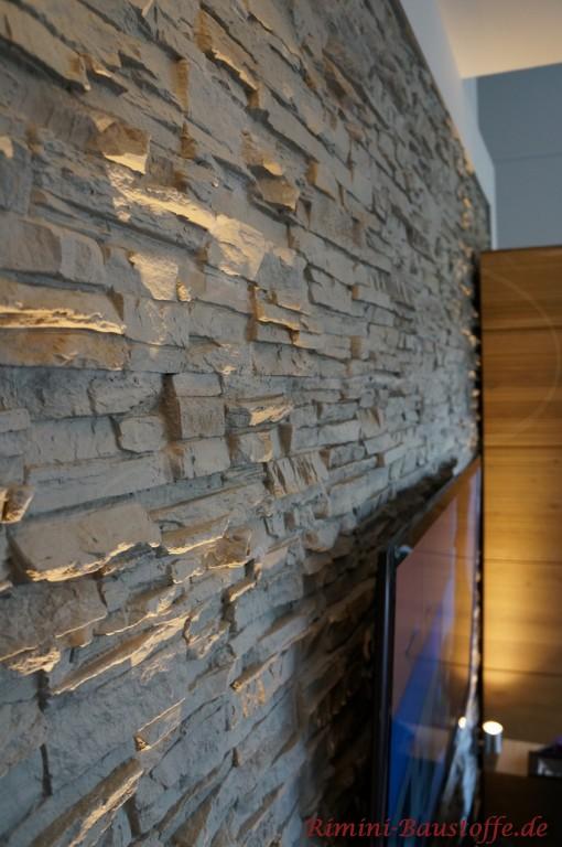 Graue Natursteinoptik hinter dem Fernseher im Wohnzimmer