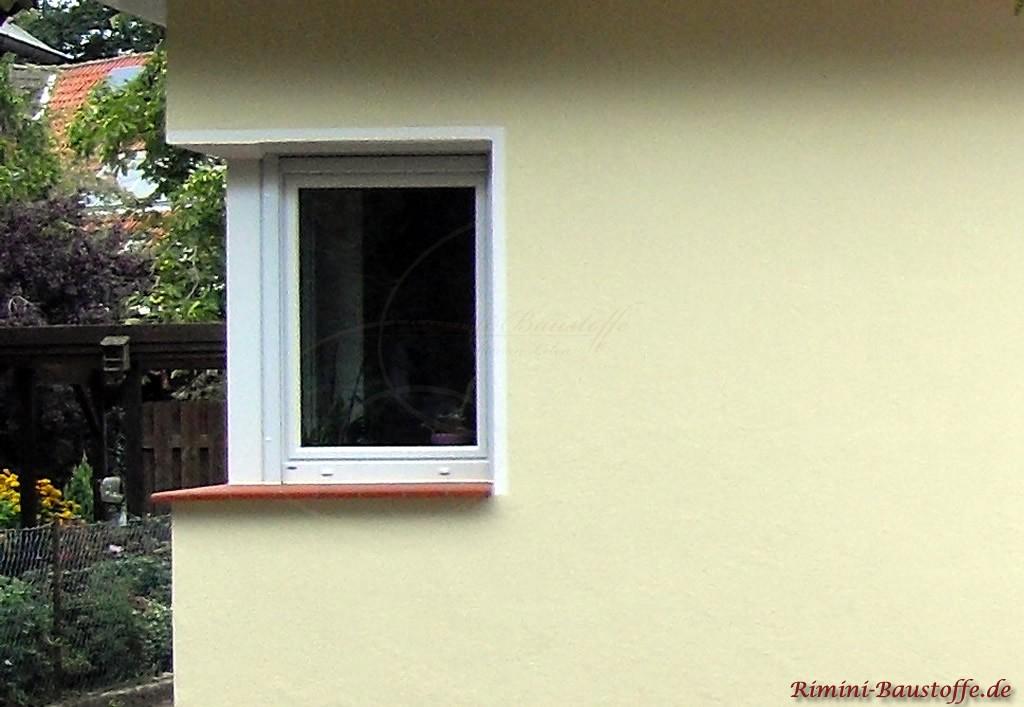 rote Tonfensterbaenke zu einer hellen gelben Fassade