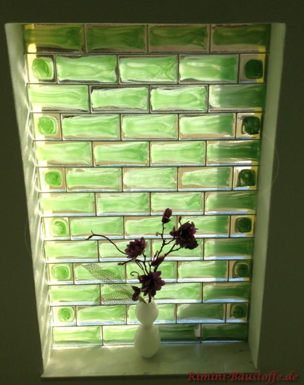 gruene Glaselemente in einer Fensternische