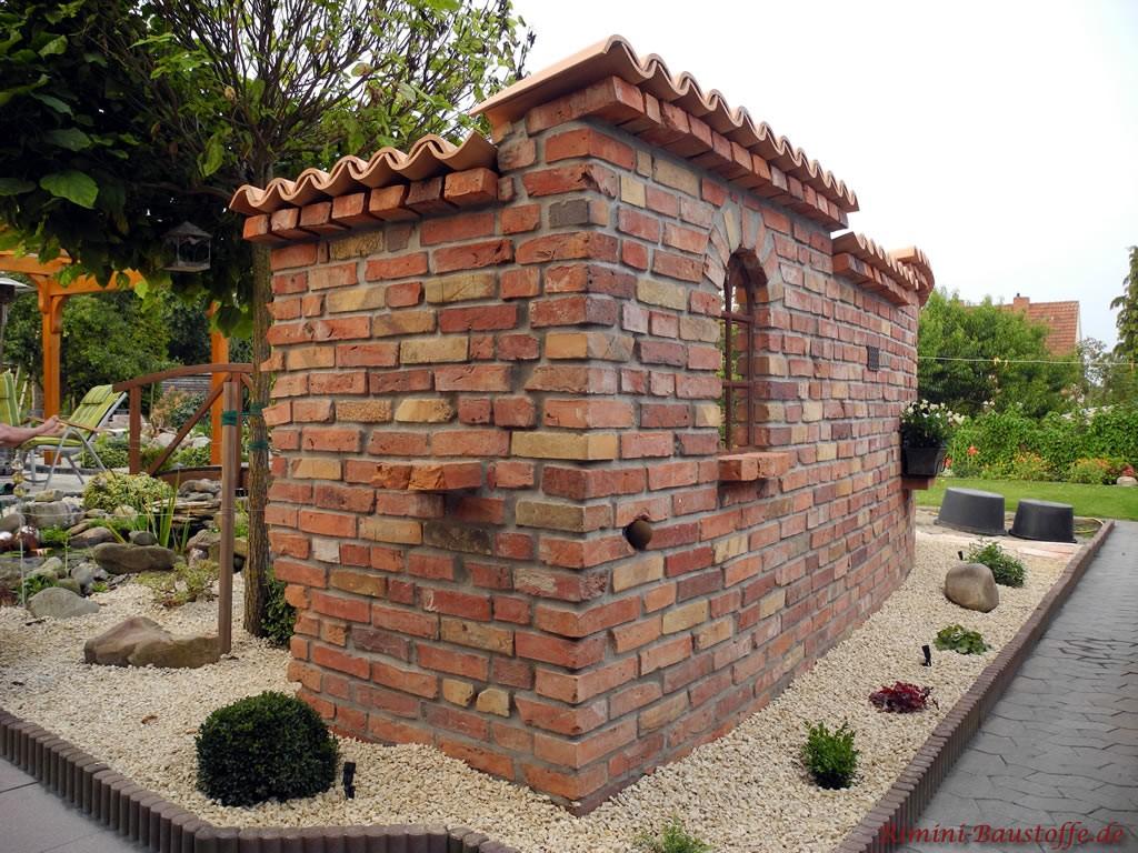 schöne rustikale freistehende Gartenmauer mit kleinen Details