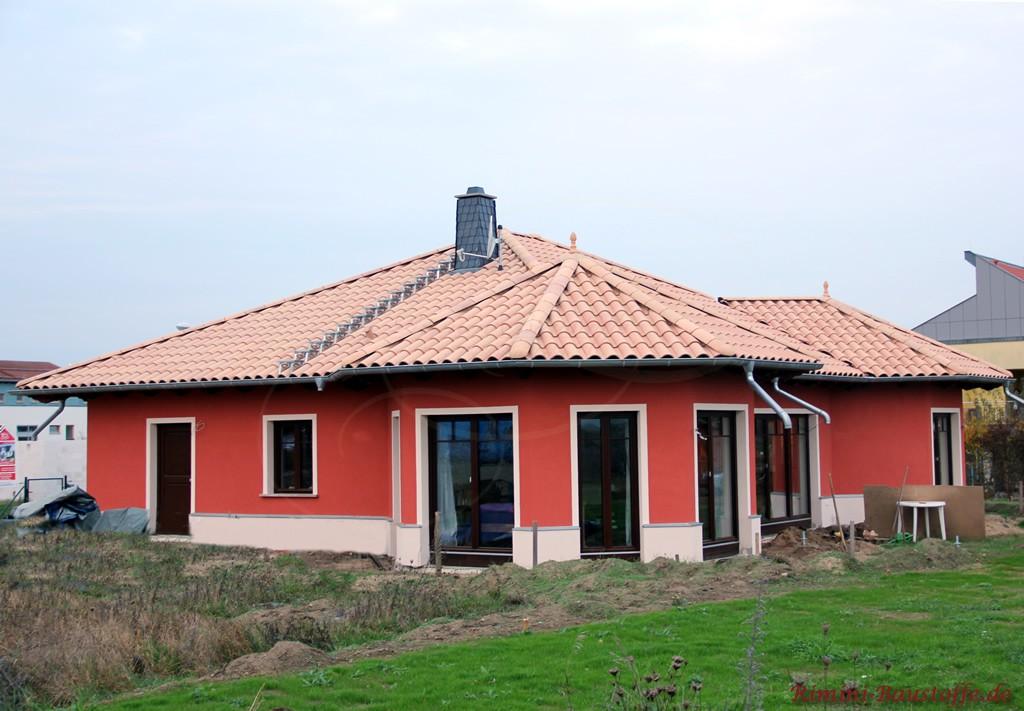 kräftige rote Putzfassade, heller Sockel und helles Dach