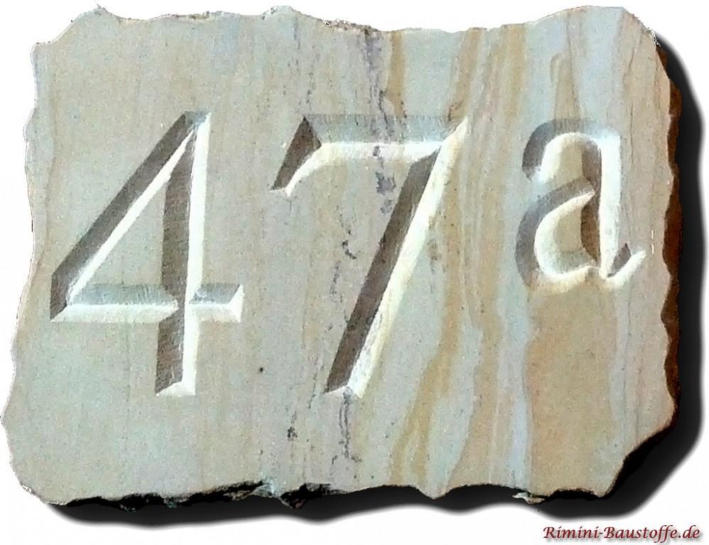 Hausnummer aus Sandstein mit Bruchsteinrand und Gravur