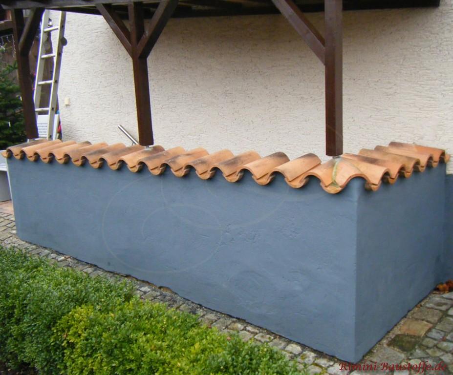Graue Mauer mit Struckturputz verkleidet und mit Halbschalen abgedeckt