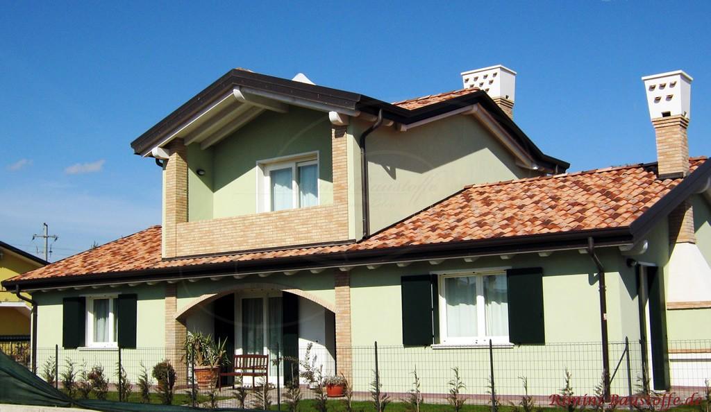 mediterranes Haus mit mintgrüner Putzfassade und bunter Ziegelmischung