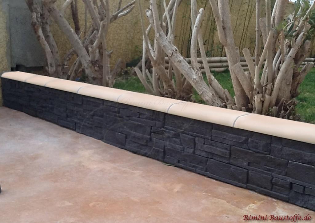 Gartenmauer mit anthrazitfarbenen Riemchen verkleidet und heller Mauerabdeckung