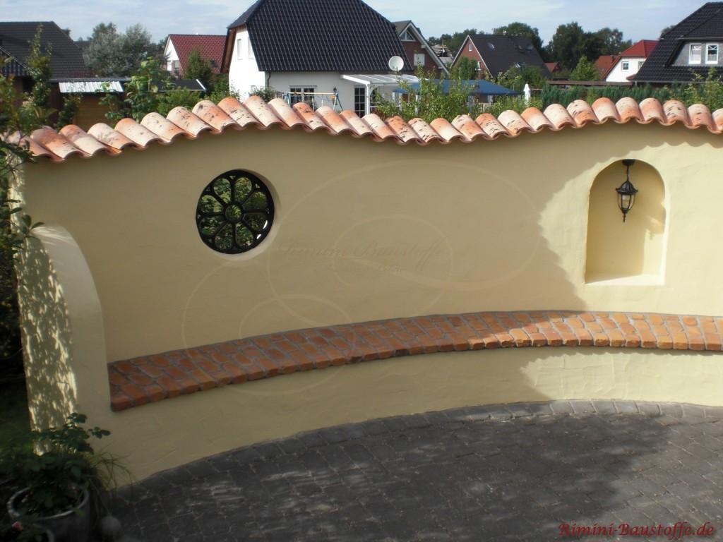 Hell verputzte Schwungmauer in beige mit schmiedeeiserne Rundfenster und schönen Ziegeln
