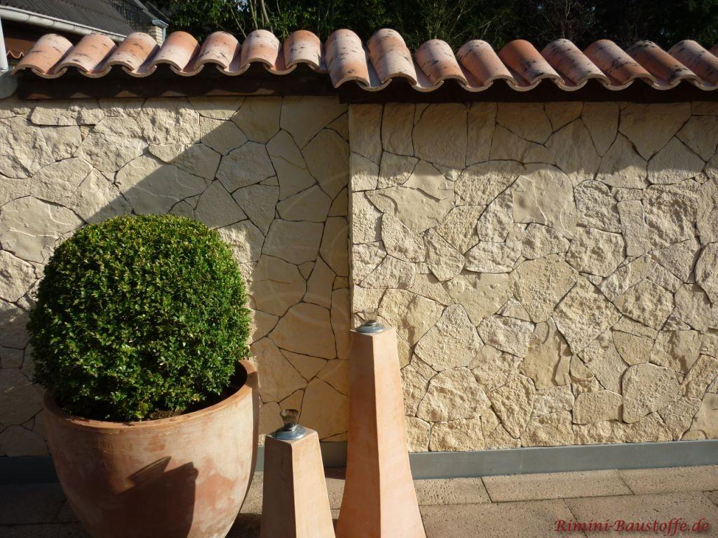 Schöne Gartenmauer mit Pflanzendeko und Dachziegeln als Abdeckung.
