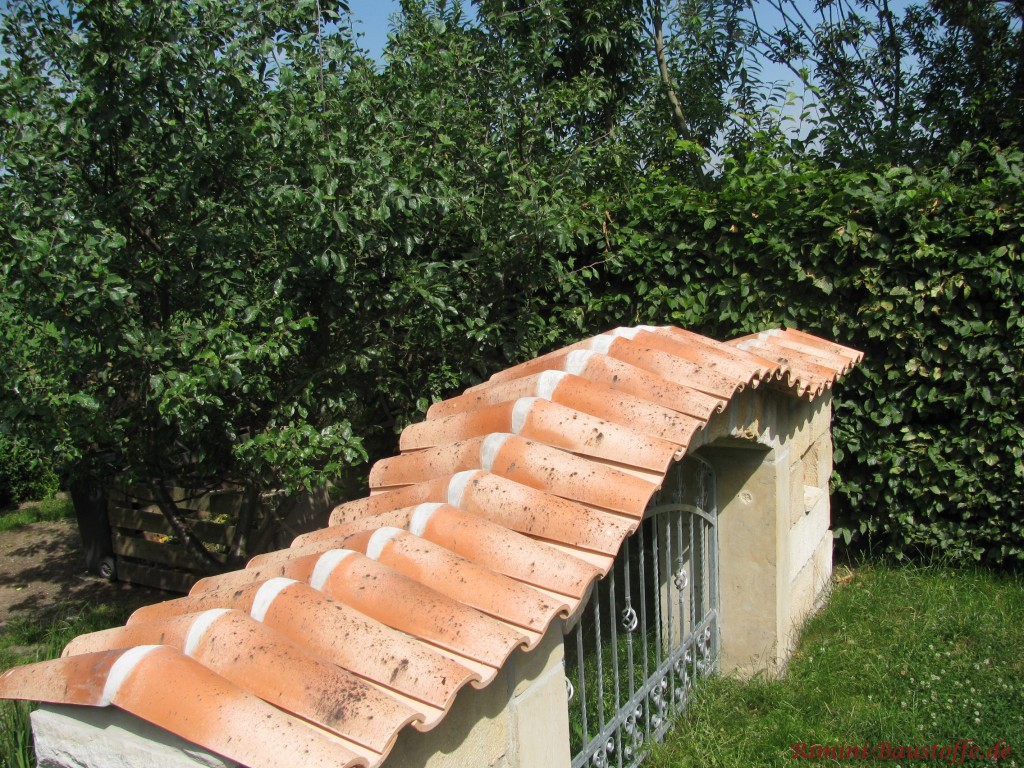Breite Sandsteinmauer mit bunten Dachziegeln abgedeckt