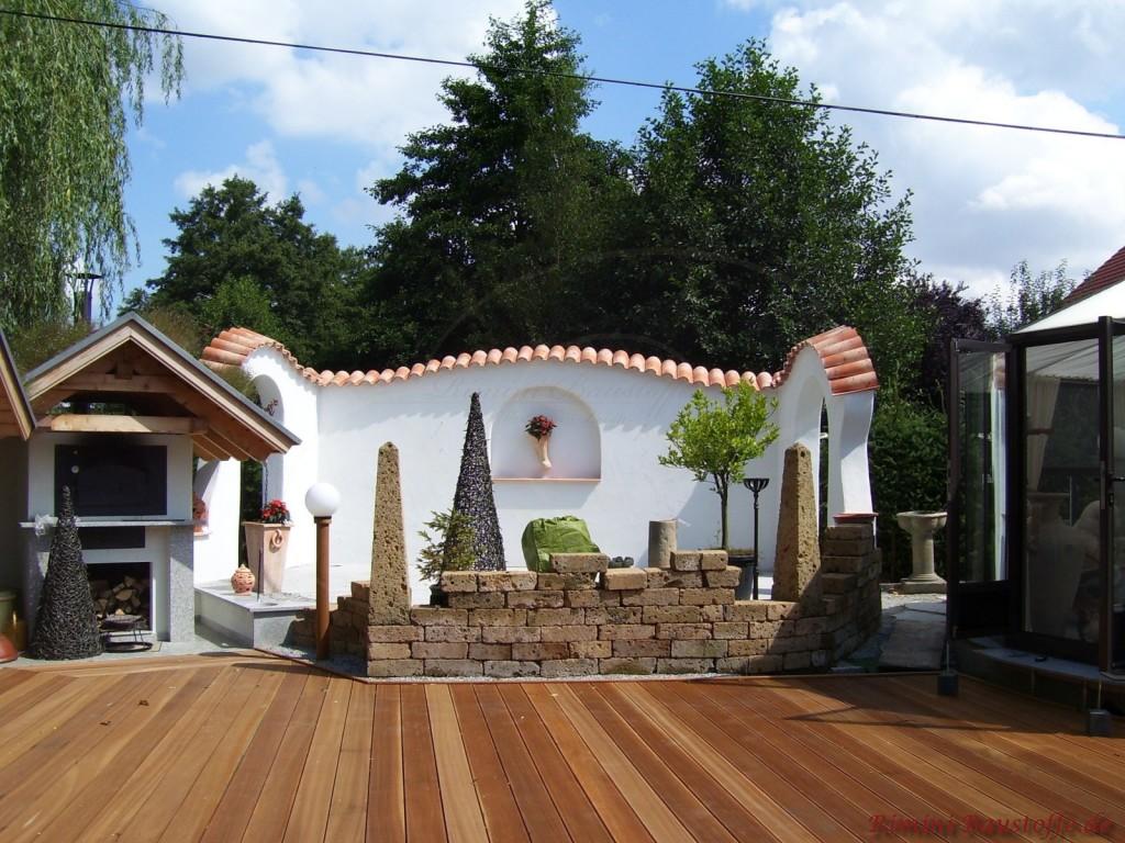Schöne Terrasse mit Holzboden, großer geschwungener Mauer mit Mauerabdeckung aus Ziegeln und einer Natursteinwand