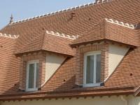 Haus mit Schindeln eingedeckt. Mit Ausbauten im Dach.