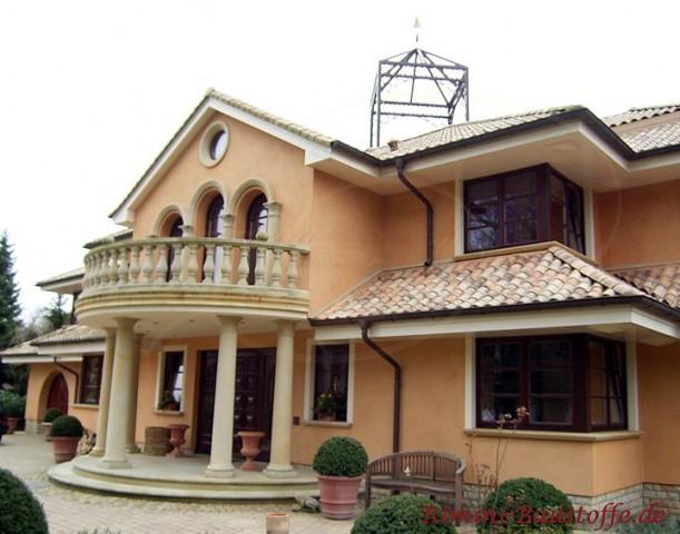 große südländische Villa mit halbrunder Balkonbrüstung und Pfeilern im Eingangsbereich