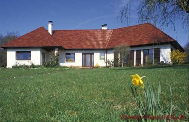 großes Wohnhaus mit weißer Putzfassade und sehr schönem dunkelroten Dach