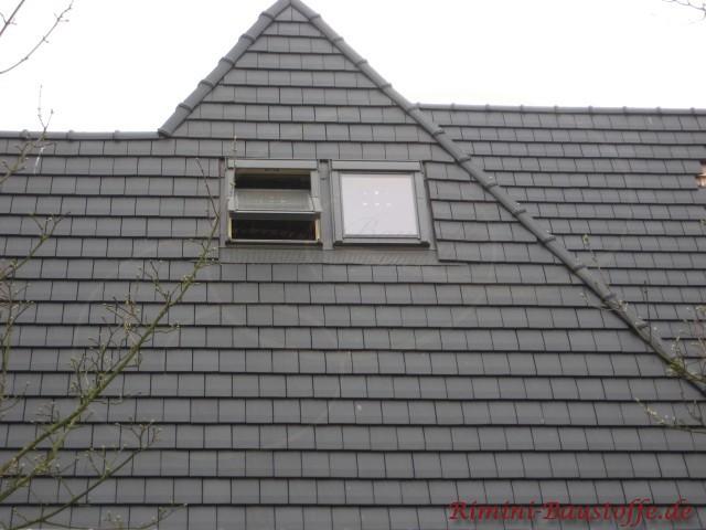 Spitzes Dach mit verscheidenen Ebenen. Es sind Dachfenster zu sehen. Das Dach wurde mit kleinen Glattziegeln in Schiefer eindeckt