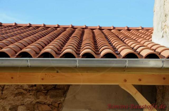 Traufe an einem Dachüberstand mit Holzbalken und einer aluminiumfarbenen Dachrinne