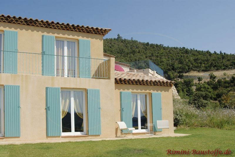 Einfamilienhaus mit hellgelber Putzfassade und milden grünen Fensterläden