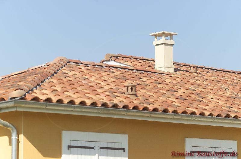 kräftige gelbe Fassade mit weißen Fenstern und hellem Schornstein zu einem schönen mediterranen Dach mit alter Oberfläche