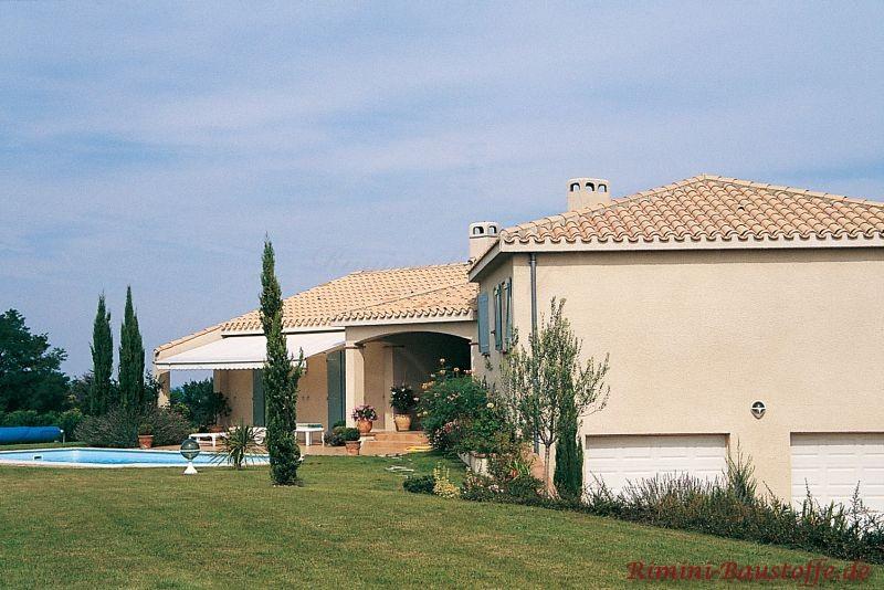 Villa im südländischen Stil mit heller Fassade und Pool im Garten