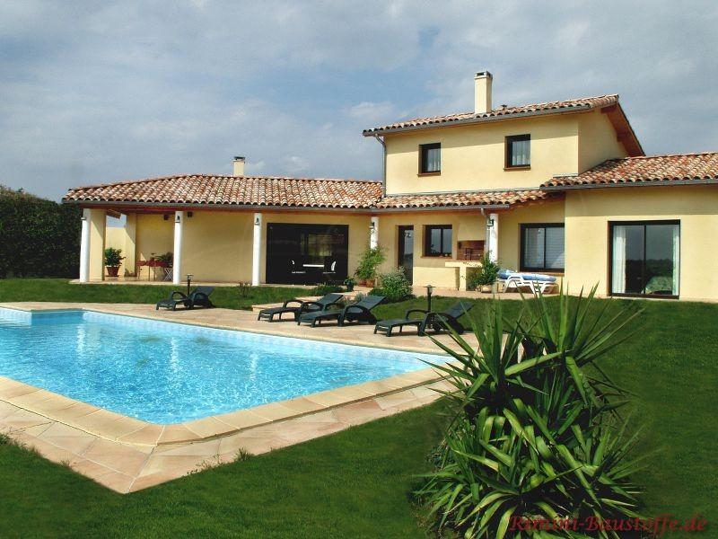 Ferienhaus im mediterranen Stil mit heller gelber Putzfassade und großem Pool im Garten