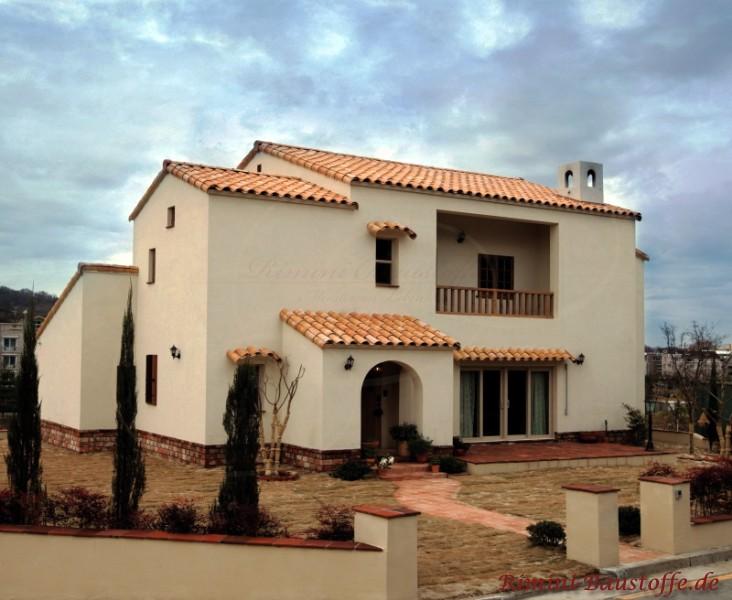 mediterrane Villa mit Putzfassade und Sockel mit Klinker