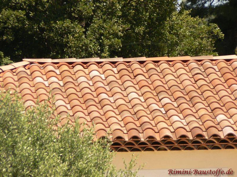 Ein Inbegriff des Mediterranen: helle Putzfassade mit schönen roten changierenden Dachziegeln mit großem Wulst