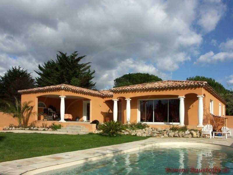 Sehr schönes Haus mit erdfarbener Putzfassade und schönem Dach. Davor sind weiße Säulen zu sehen