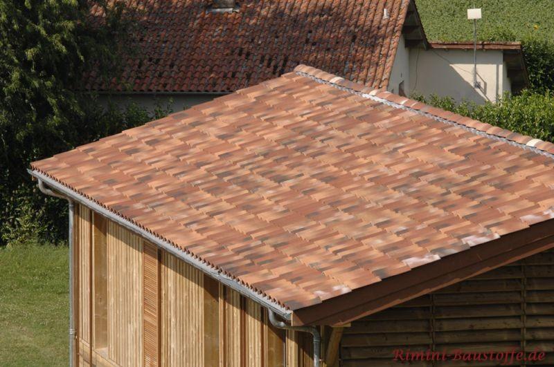 Gartenhaus aus Holz mit schönem Dach in verschiedenen Rottönen