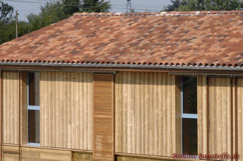 schönes kleines Holzhaus im Garten im mediterranen Stil durch das Dach in mehreren Rottönen