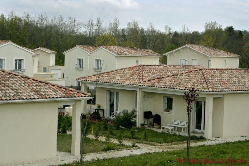 Wohnanlage mit mehreren Häusern im südländischen Stil durch die helle Putzfassade, Pfeiler und einem schönen Dach